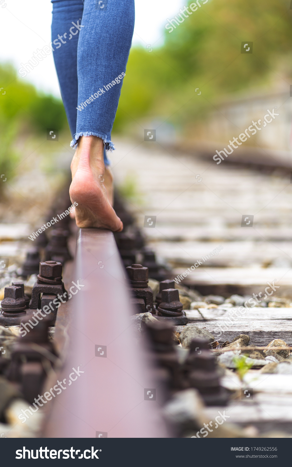 https://image.shutterstock.com/shutterstock/photos/1749262556/display_1500/stock-photo-a-vertical-shot-of-a-female-in-jeans-walking-through-the-train-rails-barefoot-1749262556.jpg