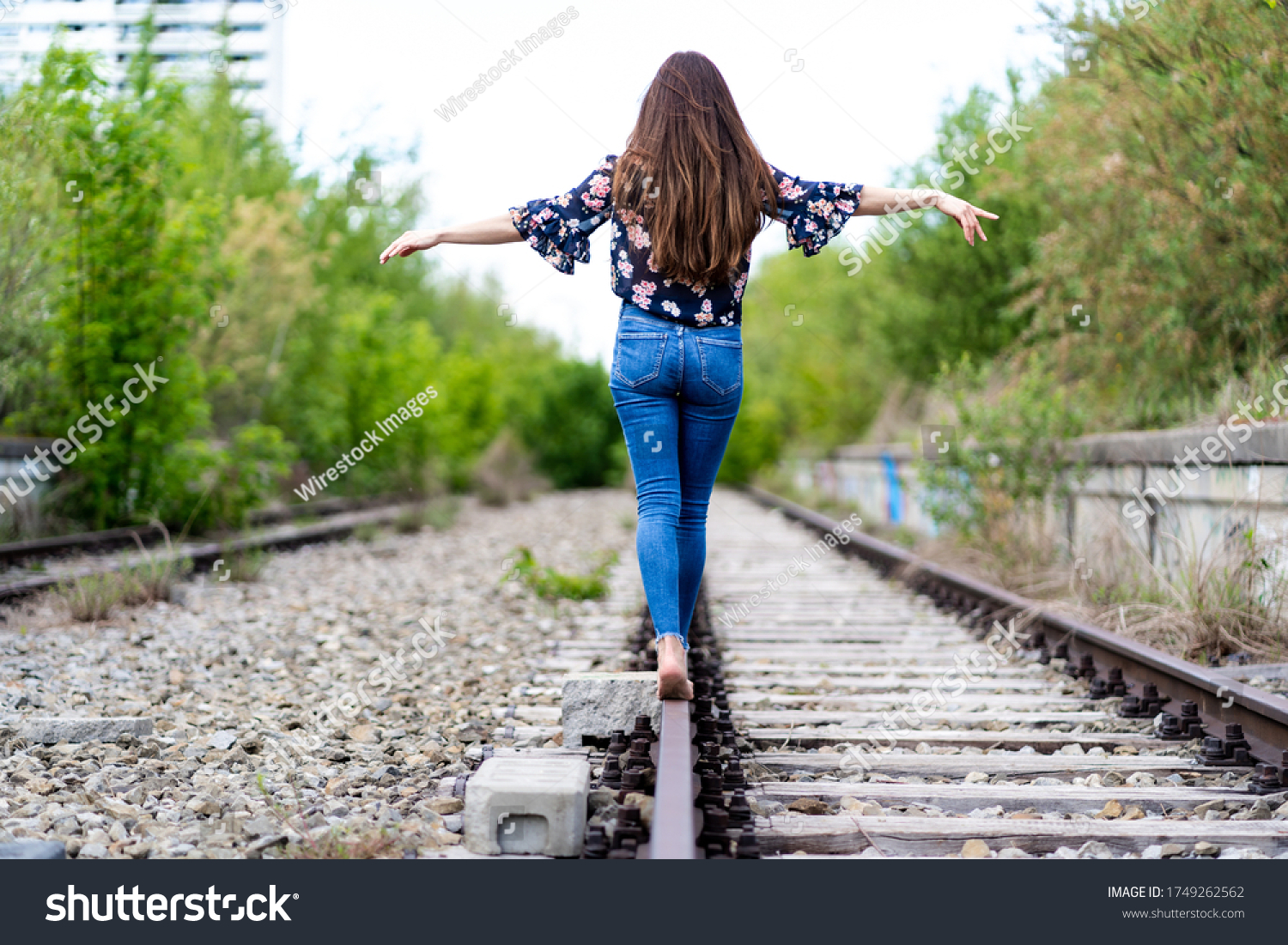 https://image.shutterstock.com/shutterstock/photos/1749262562/display_1500/stock-photo-the-back-of-a-young-female-walking-through-the-train-rails-barefoot-and-trying-to-hold-the-balance-1749262562.jpg