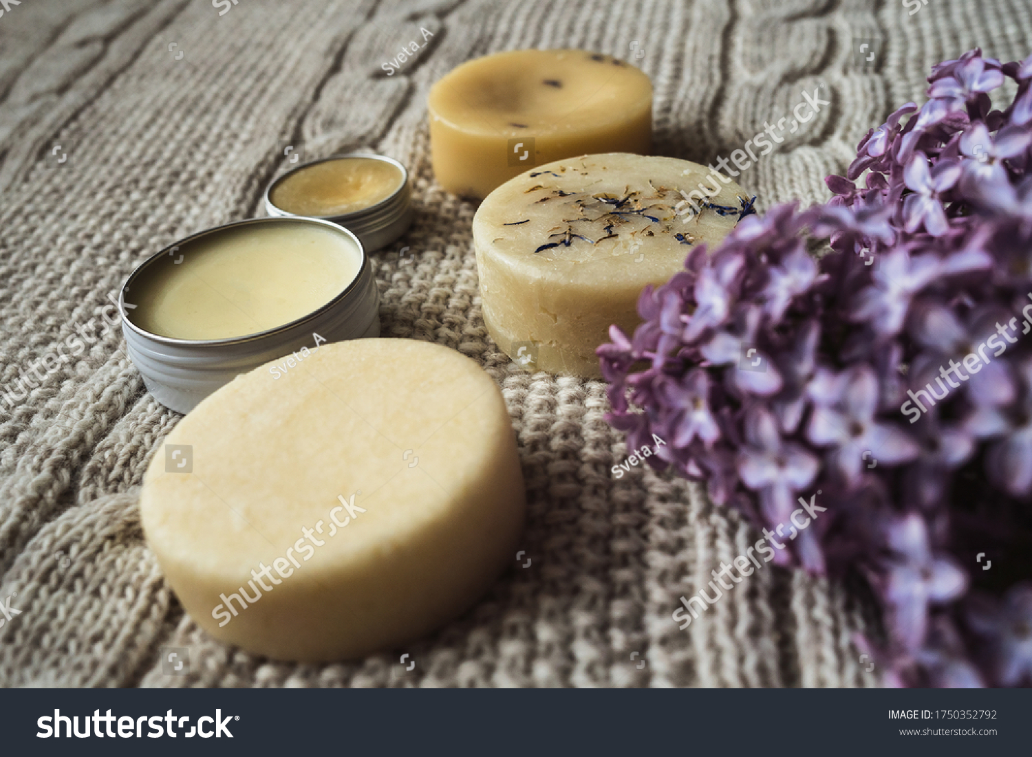 Eco-friendly unpacked homemade cosmetics. Solid shampoo, homemade soap, hair conditioner, hand cream and handmade lip balm in an aluminum jar lie on a knitted woolen beige plaid near by lilac branch. #1750352792