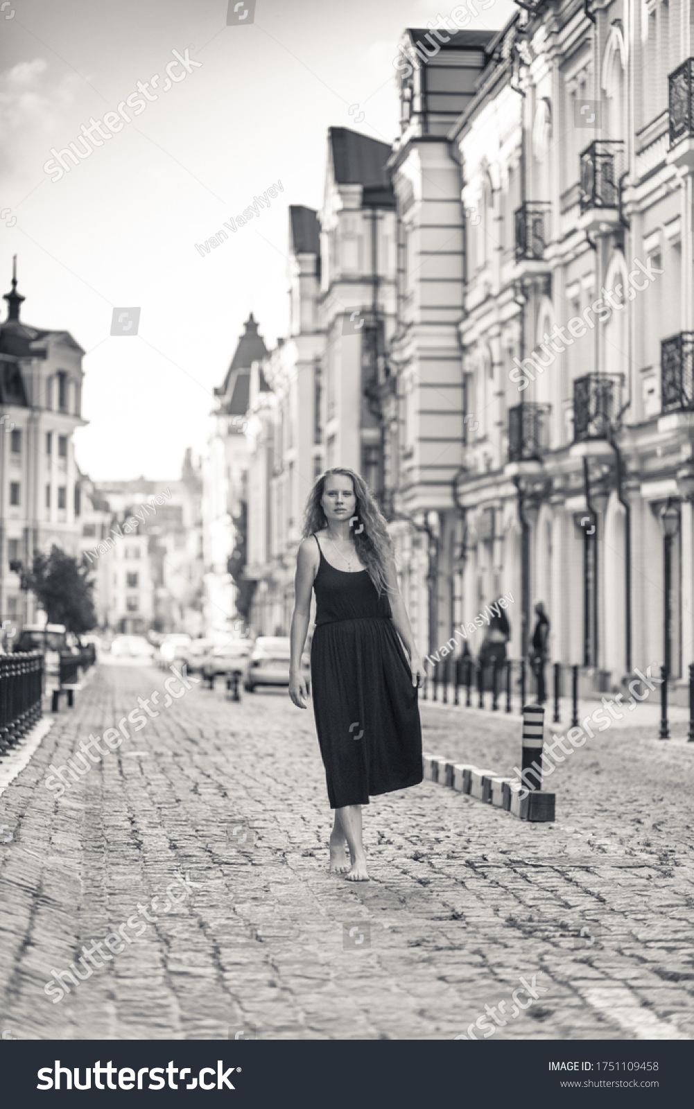 https://image.shutterstock.com/z/stock-photo-a-beautiful-woman-dressed-in-a-black-dress-and-with-long-hair-is-walking-on-the-stones-the-girl-is-1751109458.jpg