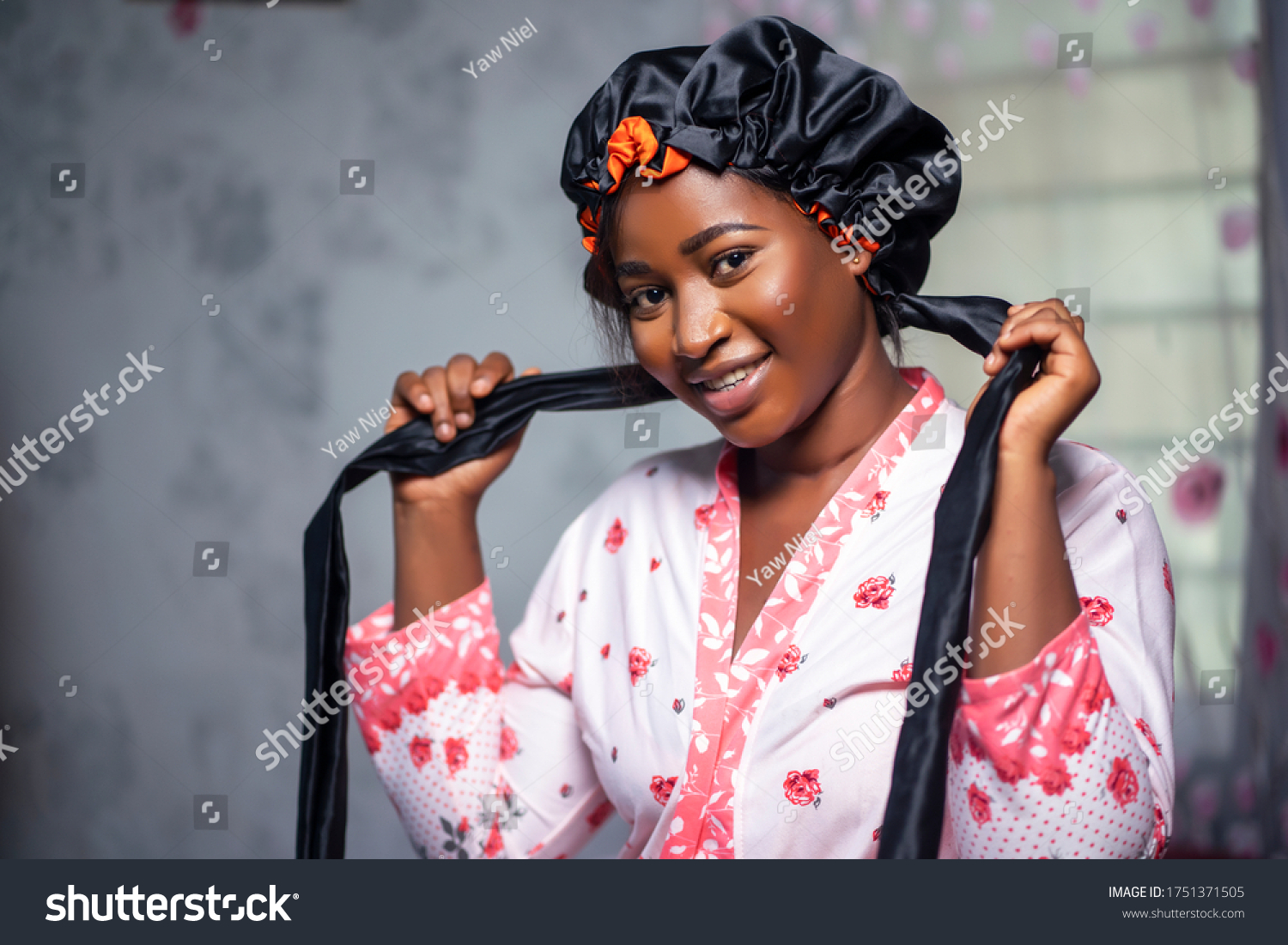 Elegant black lady looking at camera wearing a satin bonnet and floral robe, smiling in interior. Black female health and wellness indoors, skin perfection and care lifestyle. #1751371505