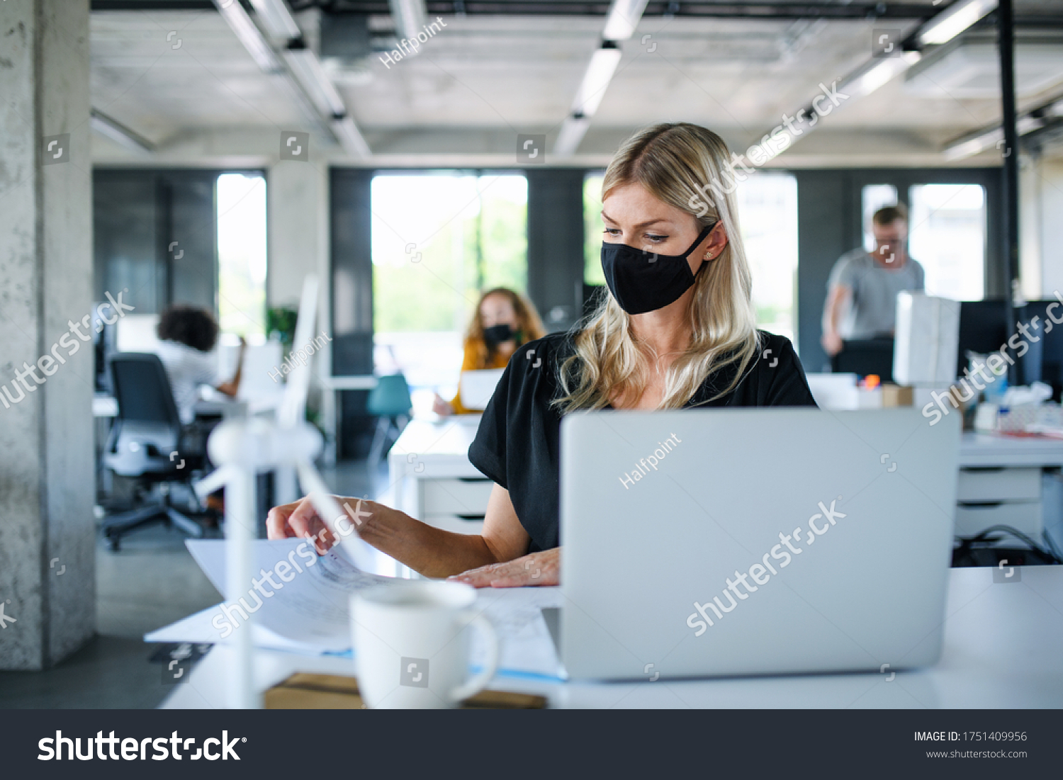 Young woman with face mask back at work in office after lockdown, working. #1751409956