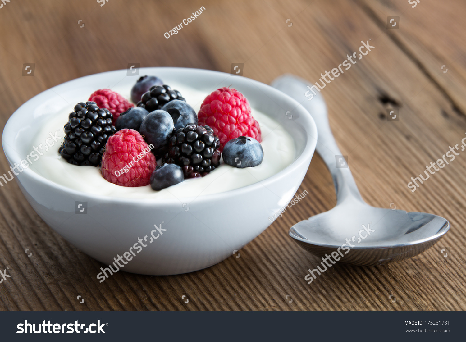 Bowl of fresh mixed berries and yogurt with farm fresh strawberries, blackberries and blueberries served on a wooden table #175231781