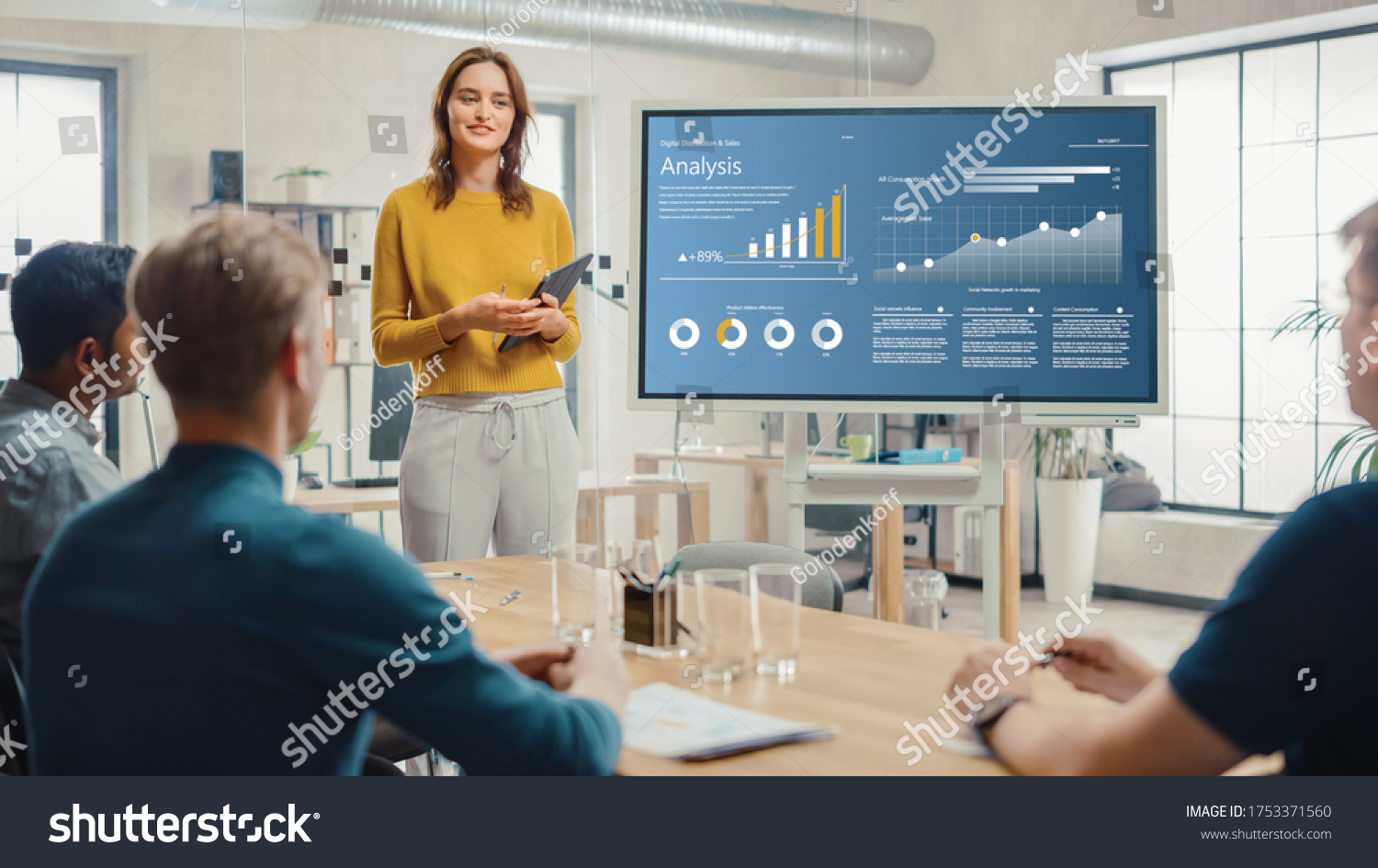 Female Chief Analyst Holds Meeting Presentation for a Team of Economists. She Shows Digital Interactive Whiteboard with Growth Analysis, Charts, Statistics and Data. People Work in Creative Office. #1753371560