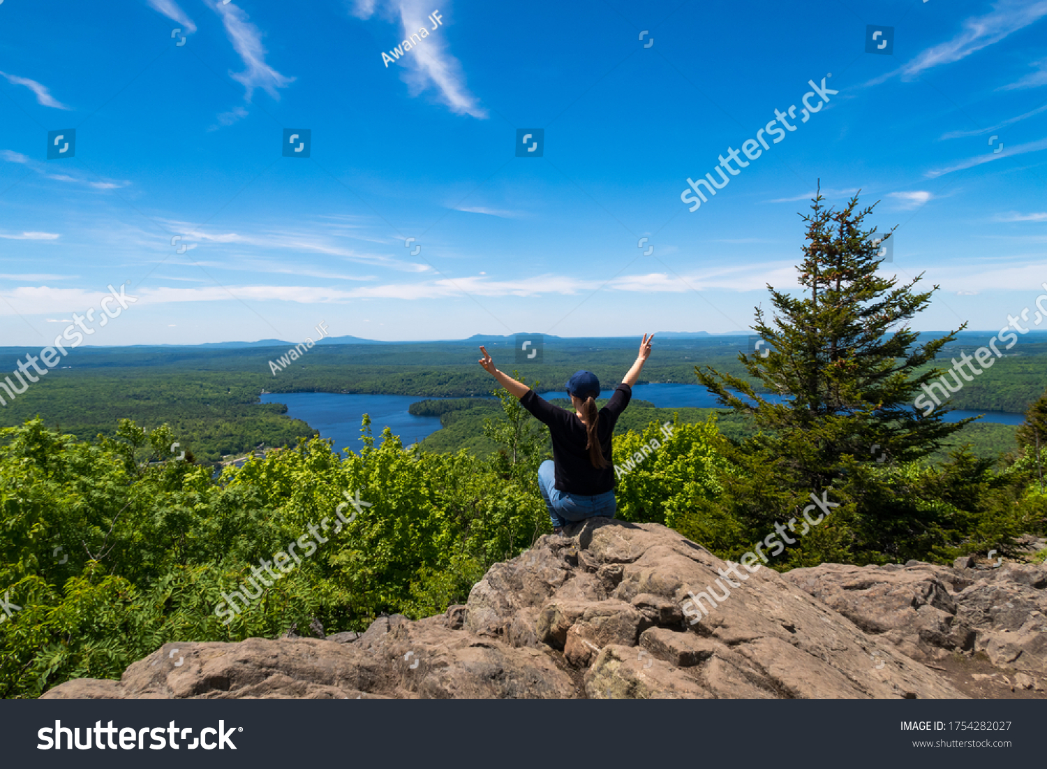 Young woman sitting at the summit of the mont-Chauve and making a peace sign with her fingers, at the Mont-Orford national park