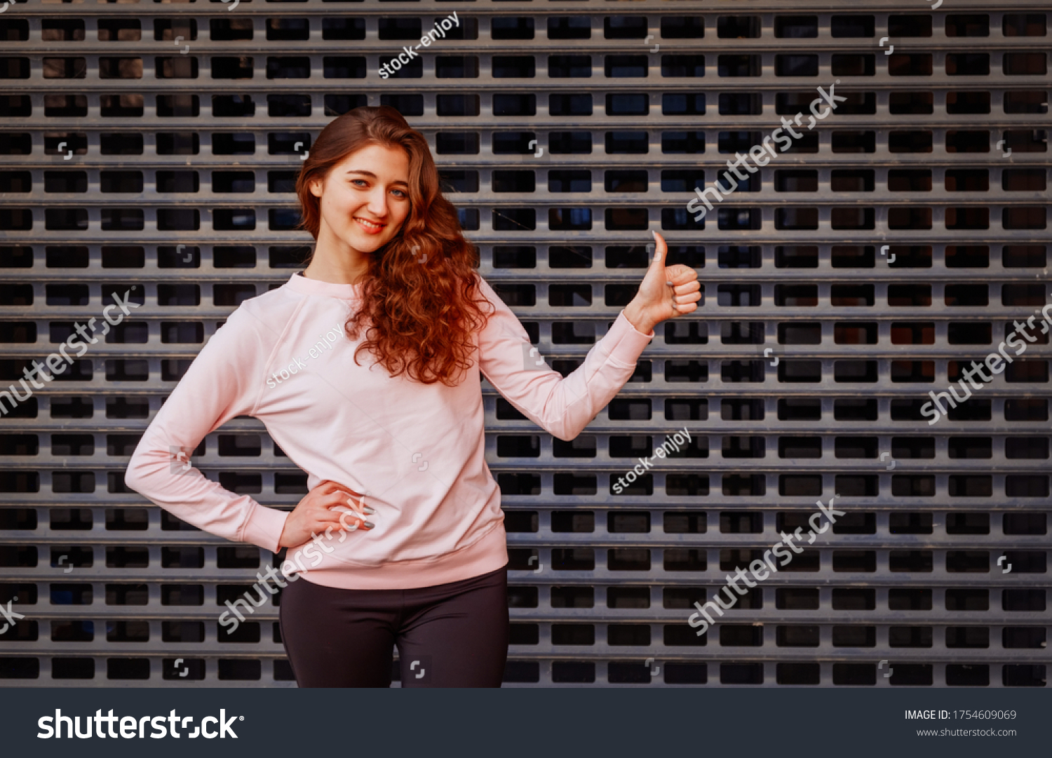 Happy redhead girl shows us thumb up sign in front of metal grid