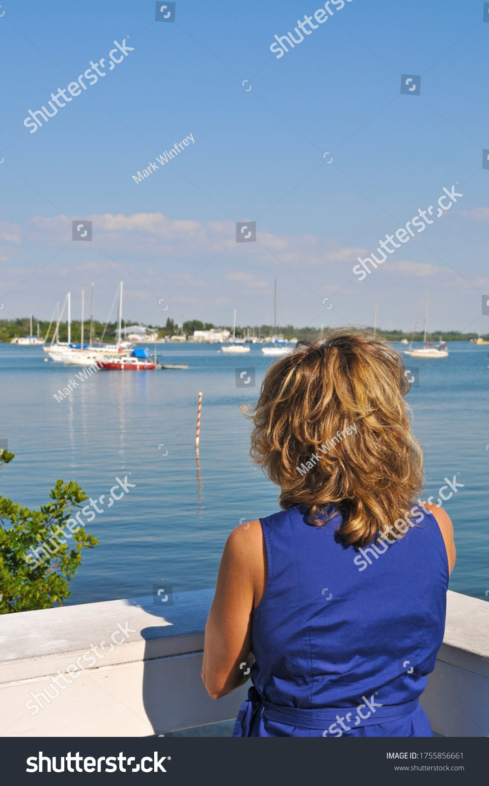 A Beautiful Woman Wearing a Blue Sun Dress Looking out at Sailboats in the Marina