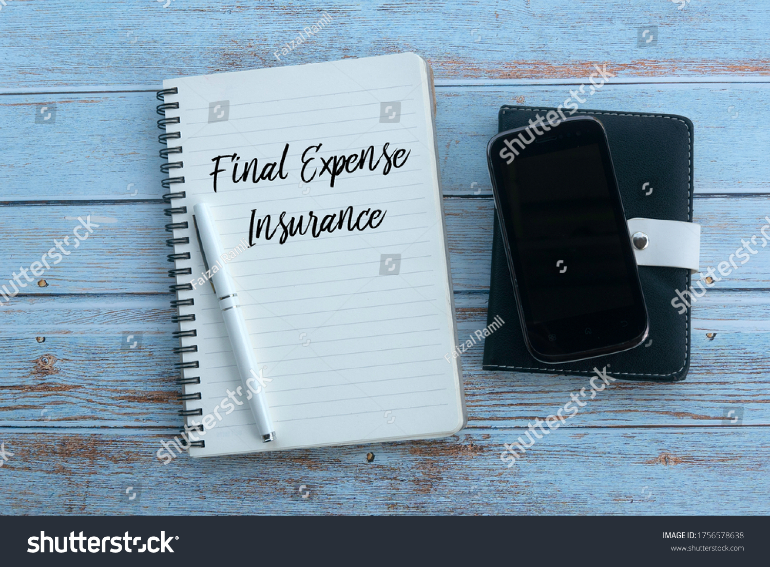 Top view of mobile phone,pen and notebook written with Final Expense Insurance on wooden background. #1756578638