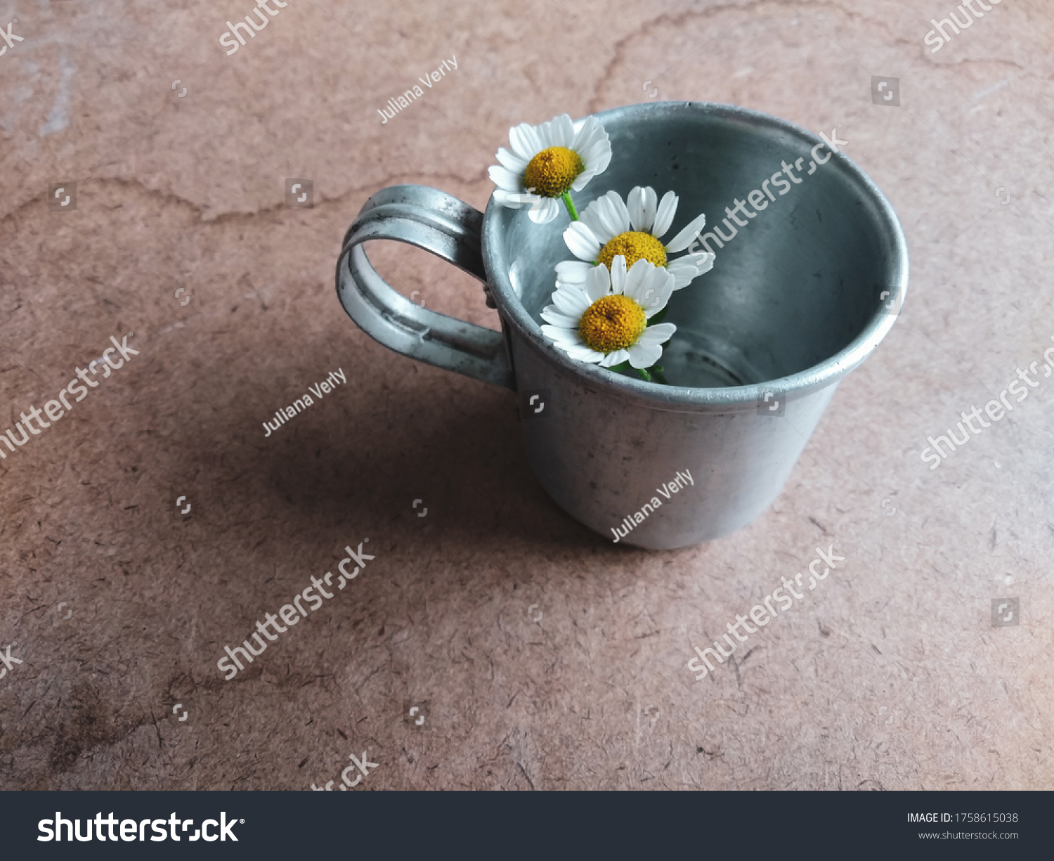 antique mug composition with small daisies on texture background