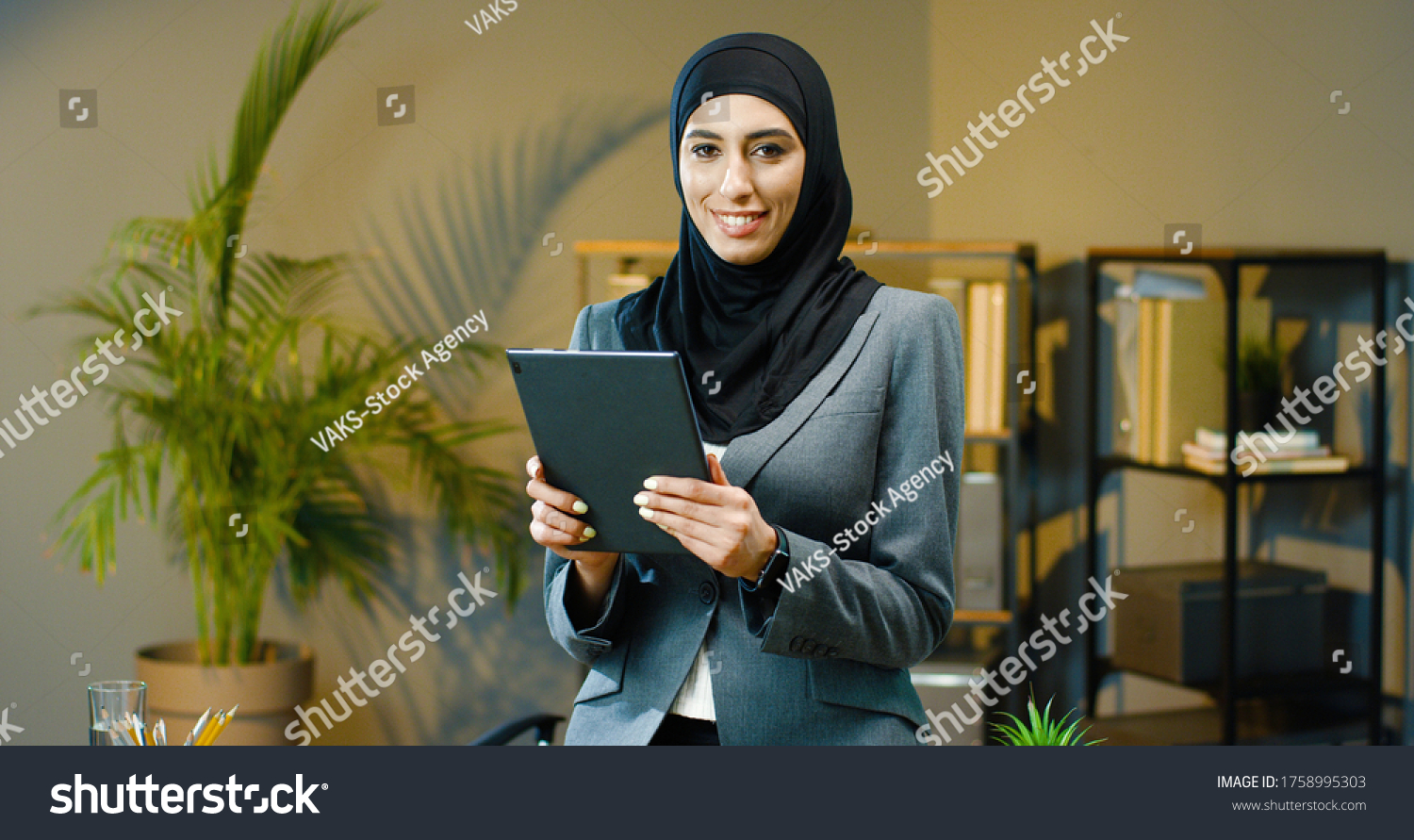 Portrait of beautiful Arab business woman using tablet in modern office. #1758995303