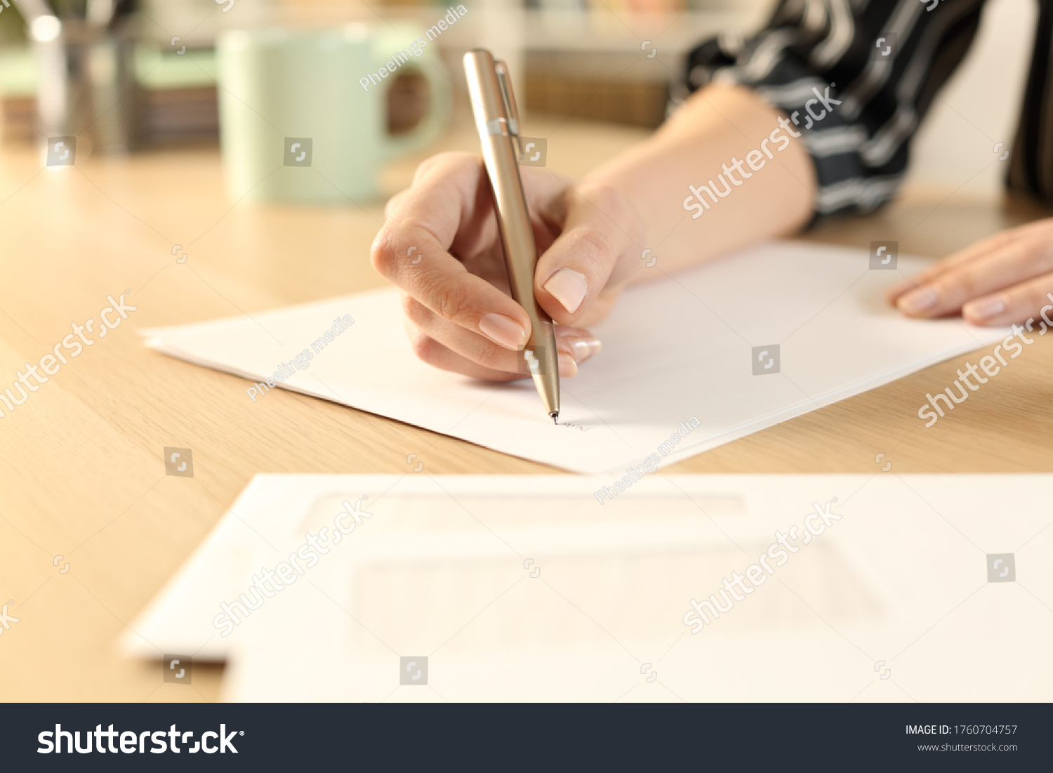 Close up of woman hands writing letter sitting on a desk #1760704757