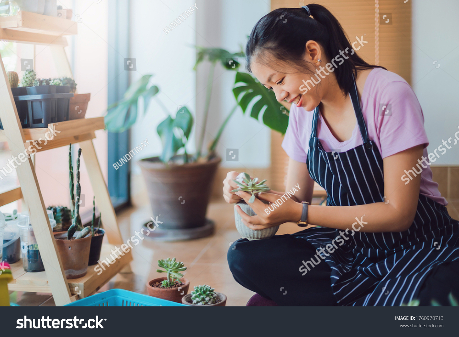 Asian young woman wearing apron caring for green indoor plant at home.New normal lifestyle concept of Hobby during quarantine and social distancing to stop spread disease of Coronavirus. #1760970713