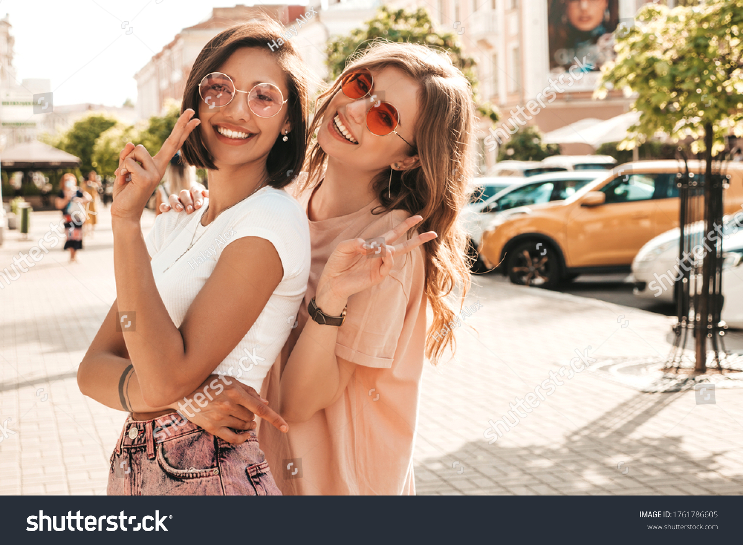 Two young beautiful smiling hipster girls in trendy summer clothes.Sexy carefree women posing on the street background in sunglasses. Positive models having fun and hugging.They going crazy #1761786605