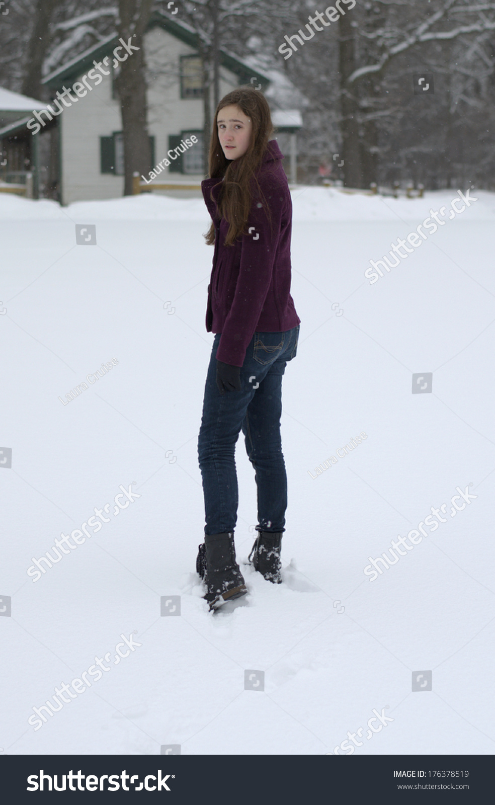 Teen Aged Girl Walking Away In The Snow Looking Back With Irritated Expression Wearing Plum