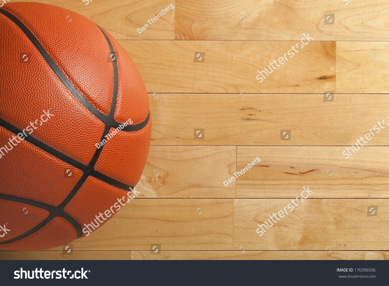 A basketball on a wood gym floor viewed from above stock for How much is it to build a basketball gym