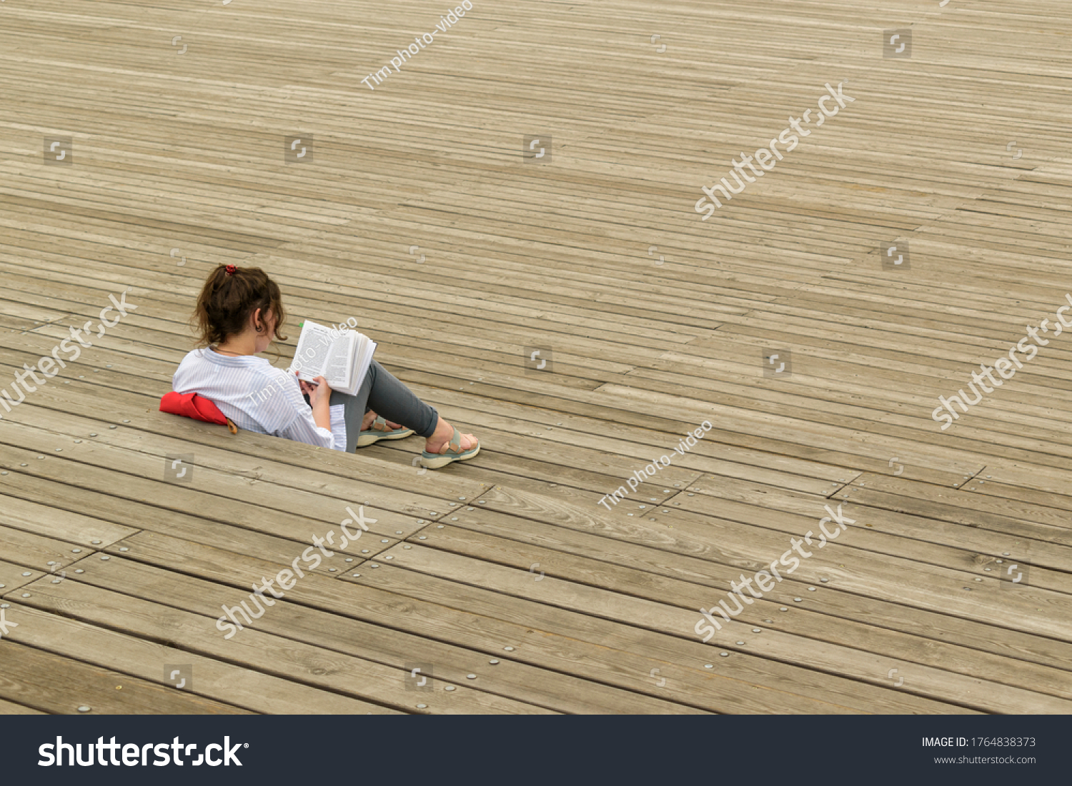 Girl is sitting on surface of wooden boards. Read book. View from the back. Hair in a bang, bangs. Concept of study, preparation for exams at the university, leisure.