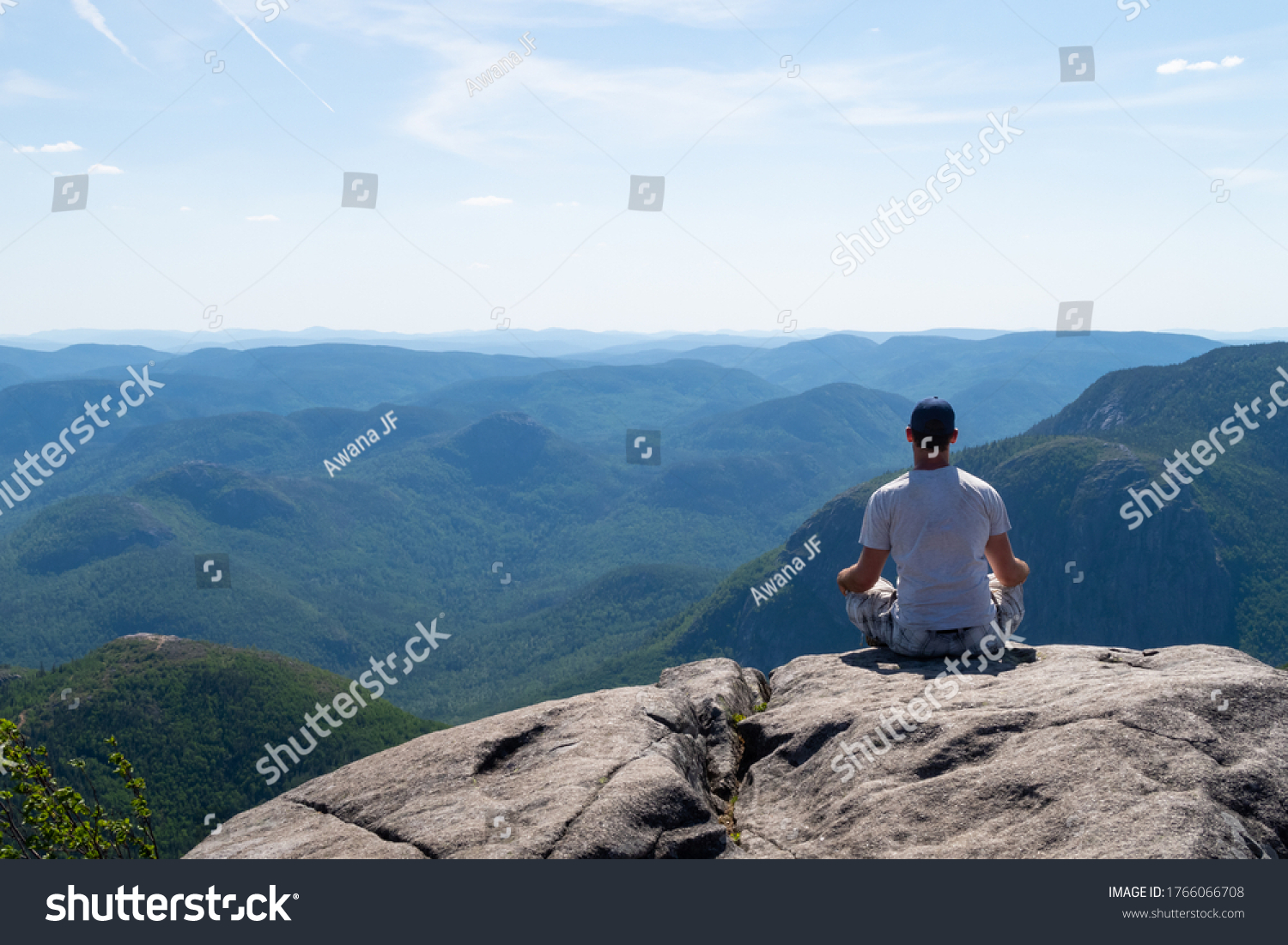 """Young man admiring the landscape at the top of the """"mont du lac des cygnes"""" (swan lake mountain) in Charlevoix, Quebec"""