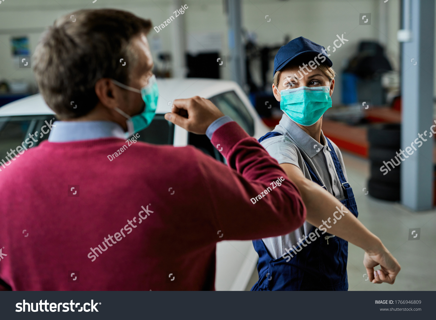 Female car mechanic and her customer greeting with elbows while wearing protective face masks in auto repair shop during coronavirus epidemic.  #1766946809