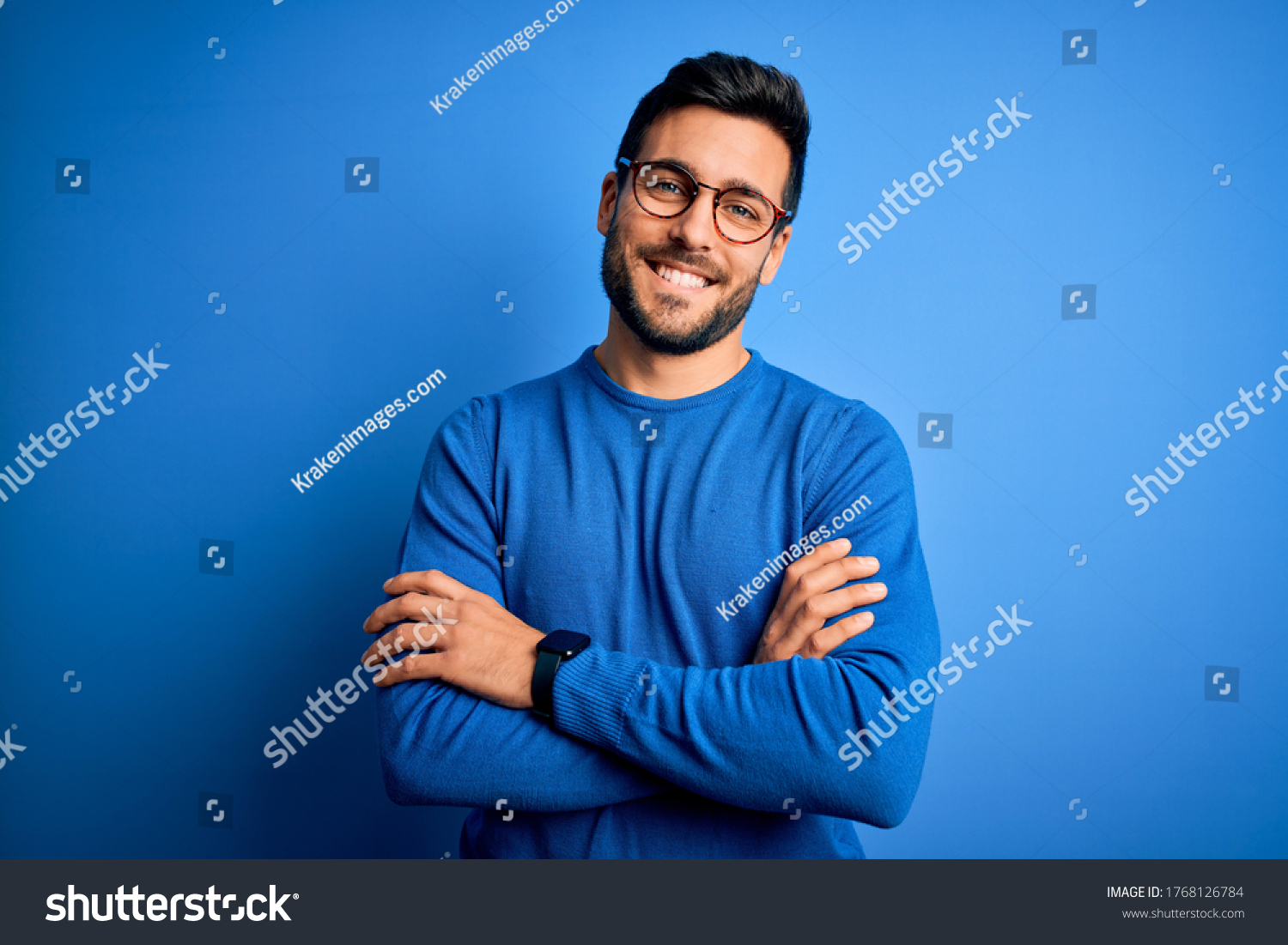 Young handsome man with beard wearing casual sweater and glasses over blue background happy face smiling with crossed arms looking at the camera. Positive person. #1768126784
