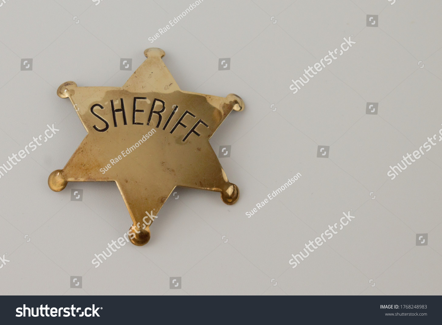 Upholland, Lancashire, UK, 02/07/2020: Brass sheriff's badge on a white background with copy space to the right