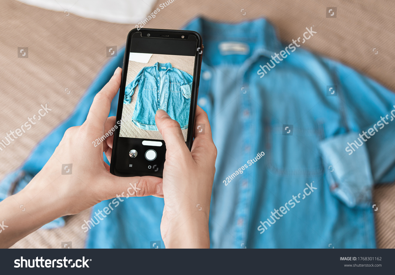Woman taking photo of denim shirt on smartphone  #1768301162