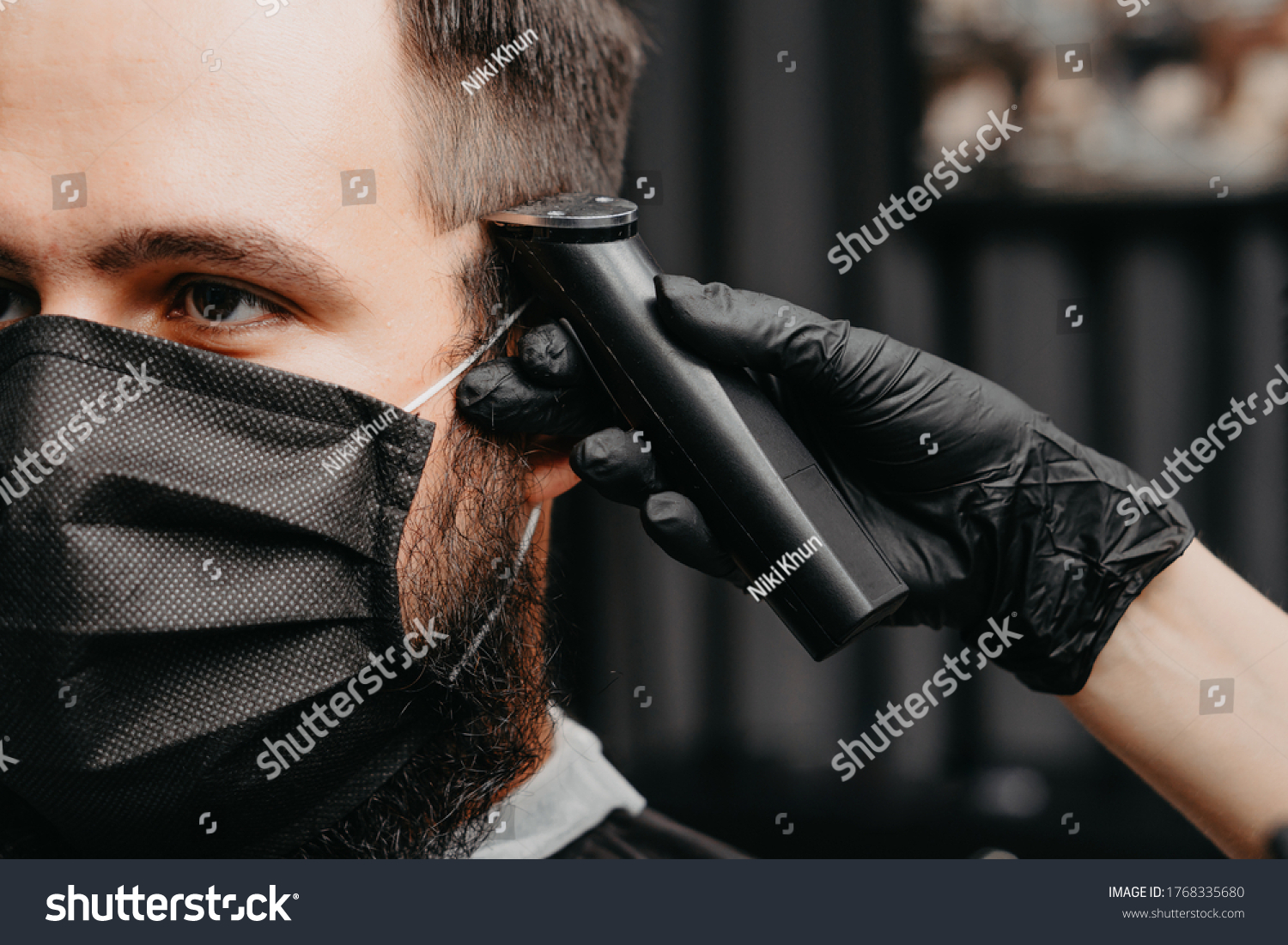 Woman barber cutting hair to a bearded man in face mask. Quarantine haircut concept. #1768335680