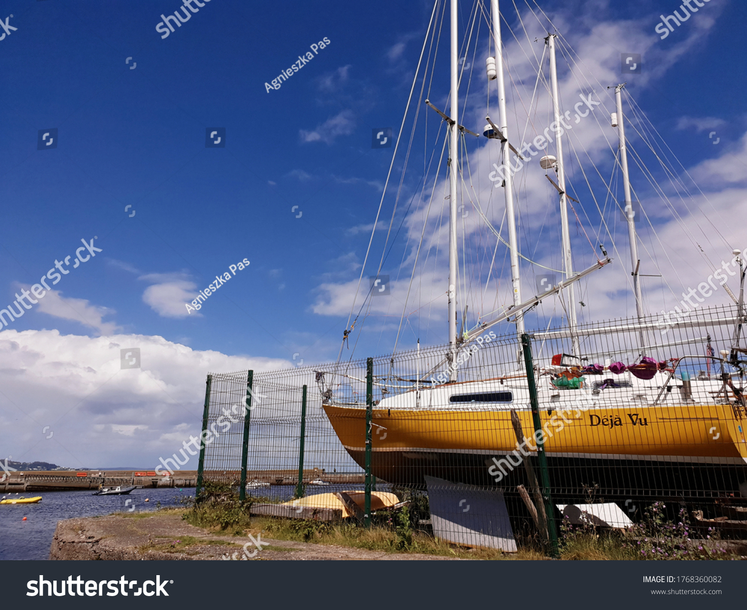 BRAY, CO. WICKLOW, IRELAND - JUNE 21, 2020: Sail boats on land in Bray port on sunny day. Colorful boats with white masts against blue sky.