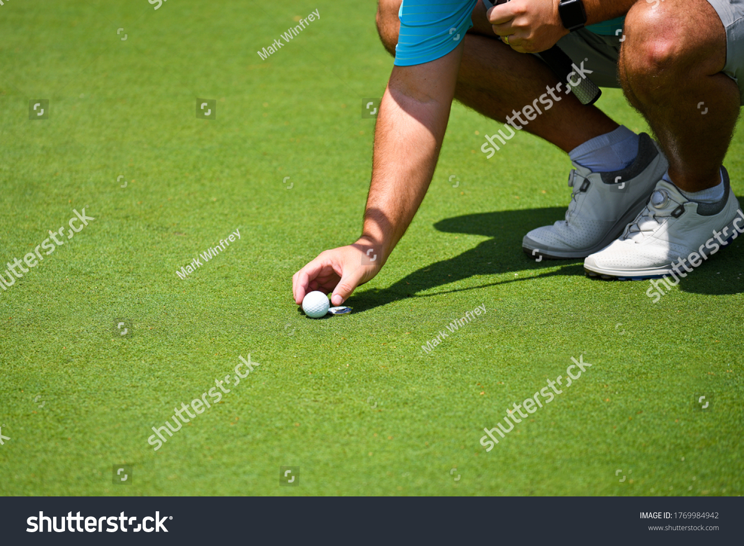 Young Man Kneeling Down and Placing his Golf Ball and Marker on the Putting Green.