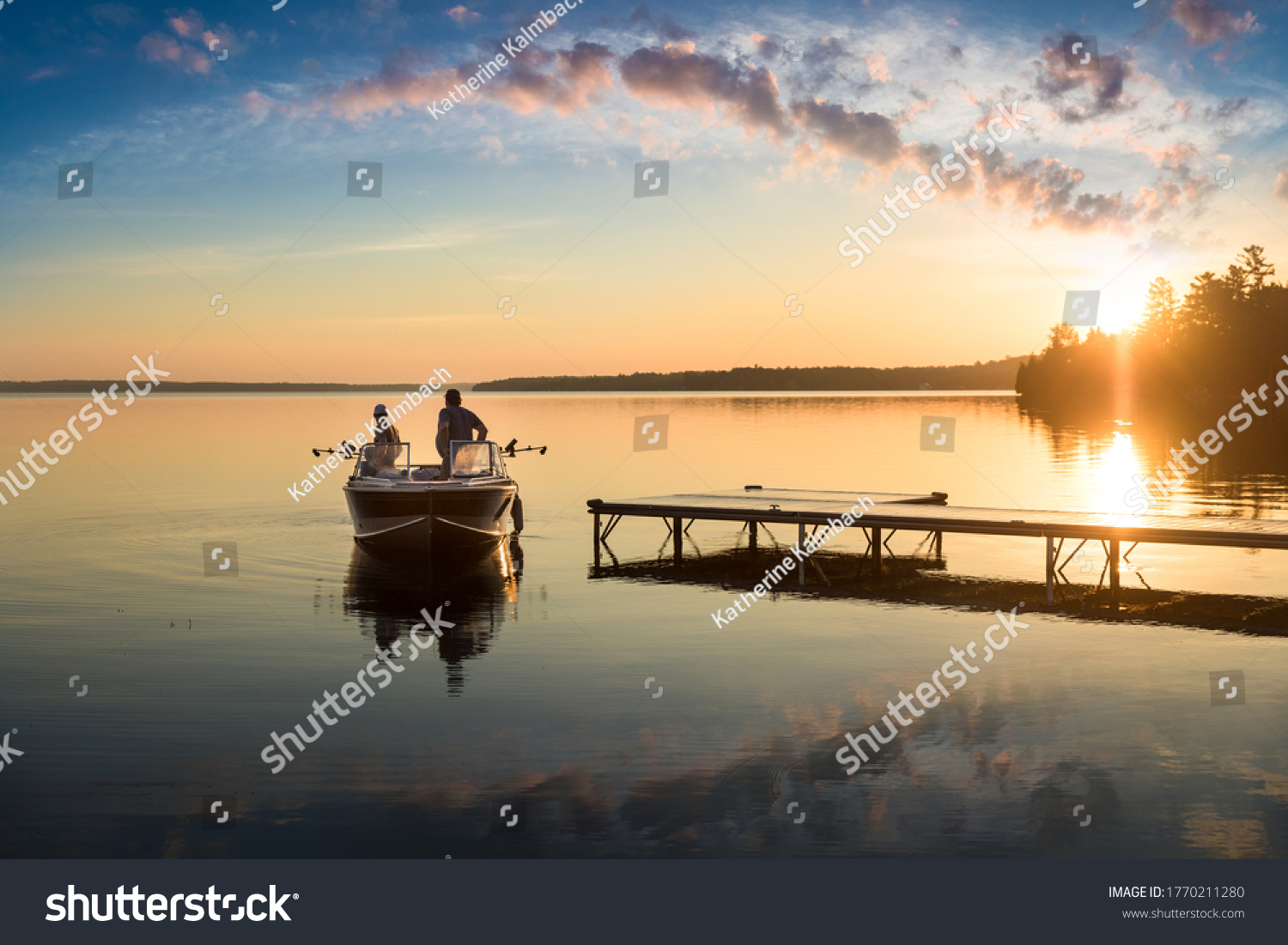 Cottage Life - Father and son fishing on a boat at sunrise/sunset at the peaceful cottage in Kawartha Lakes Ontario Canada on Balsam Lake #1770211280