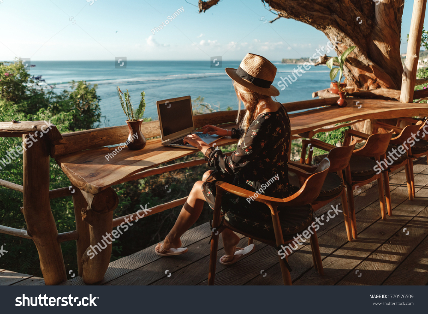 Freelance concept. Pretty young woman using laptop in cafe on tropical beach in outdoor cafe terrace with sea view. Work and travel #1770576509