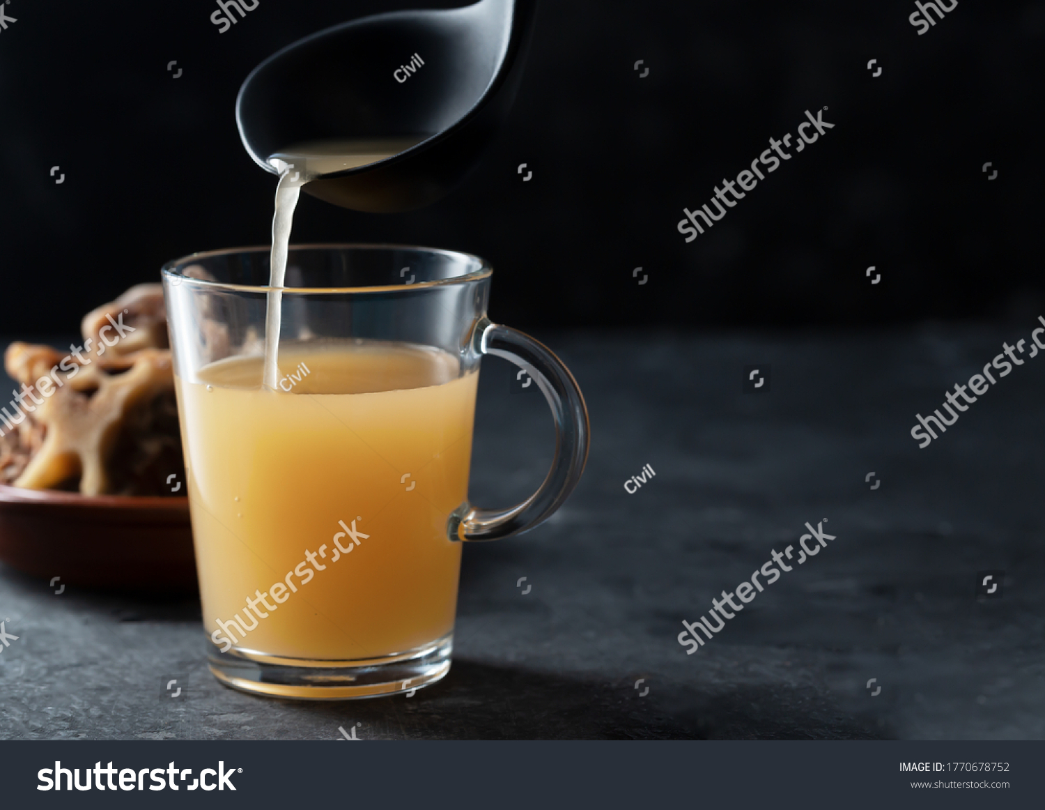 Homemade Beef Bone Broth in Glass Storage Jar on the black background. Bones contain collagen, which provides the body with amino acids, which are the building blocks of proteins #1770678752