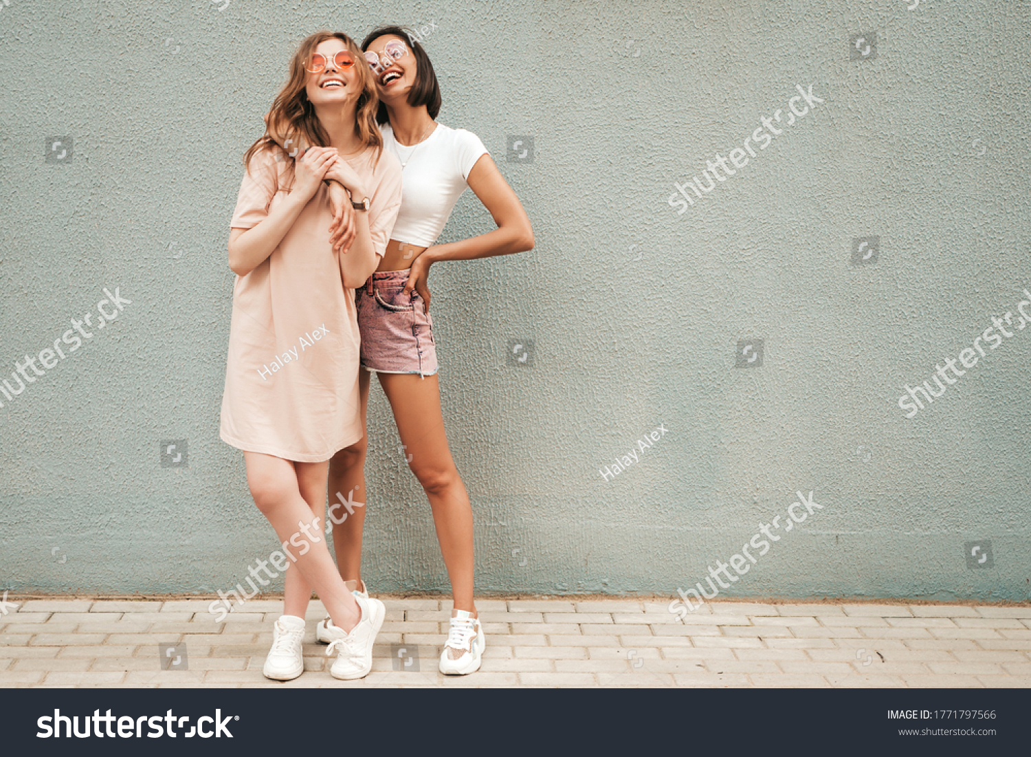 Two young beautiful smiling hipster girls in trendy summer clothes.Sexy carefree women posing on street background in sunglasses. Positive models having fun and hugging #1771797566