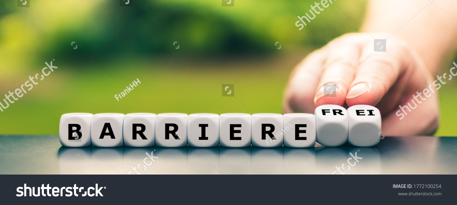 """Hand turns dice and changes the German word """"Barriere"""" (barrier) to """"Barrierefre"""" (barrier free). #1772100254"""
