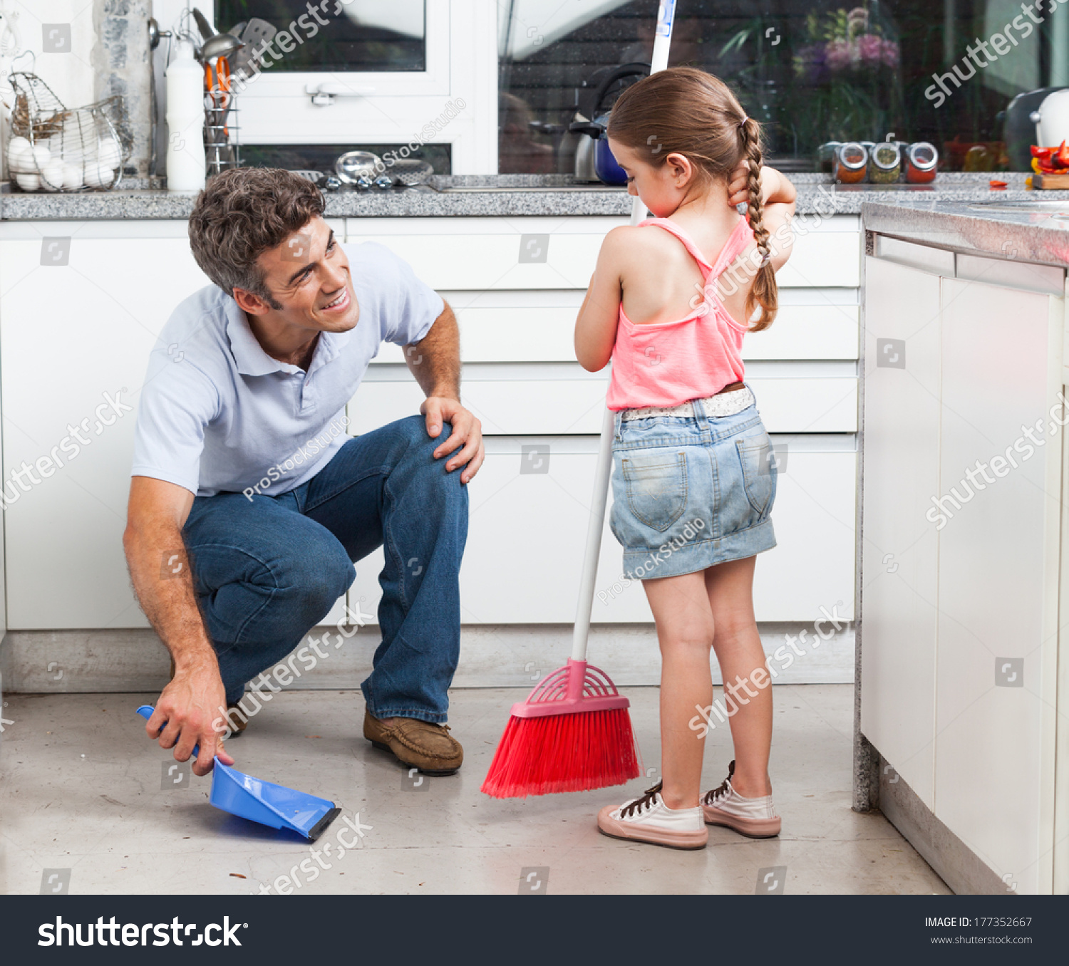 Sweep the kitchen floor - Father And Daughter Cleaning In The Kitchen Sweep Floor At Home Man Little Girl