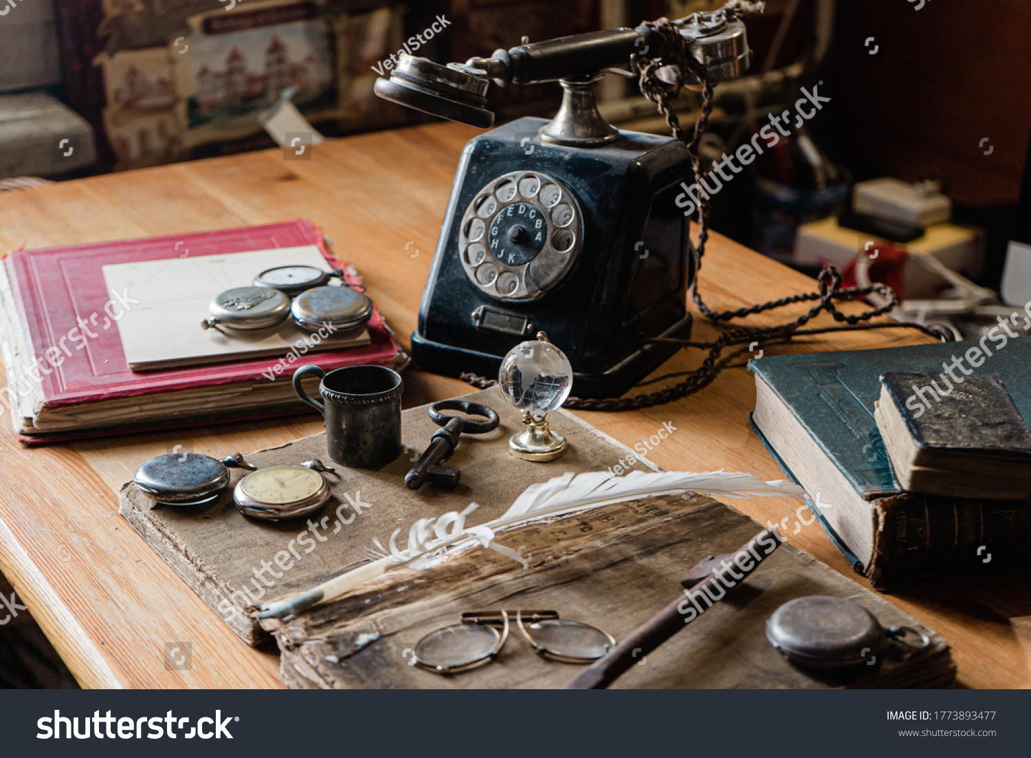 antique desk with accessories: old telephone, books, globe, notes, ink pen, old glasses. and for hours. The picture conveys the atmosphere of antiquity - past years #1773893477