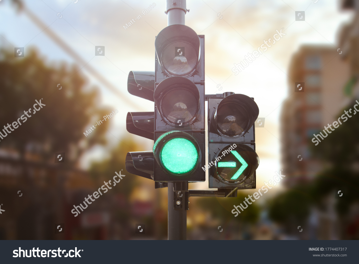 Green traffic light with green arrow light up in city while sunset allows car to turn right #1774407317
