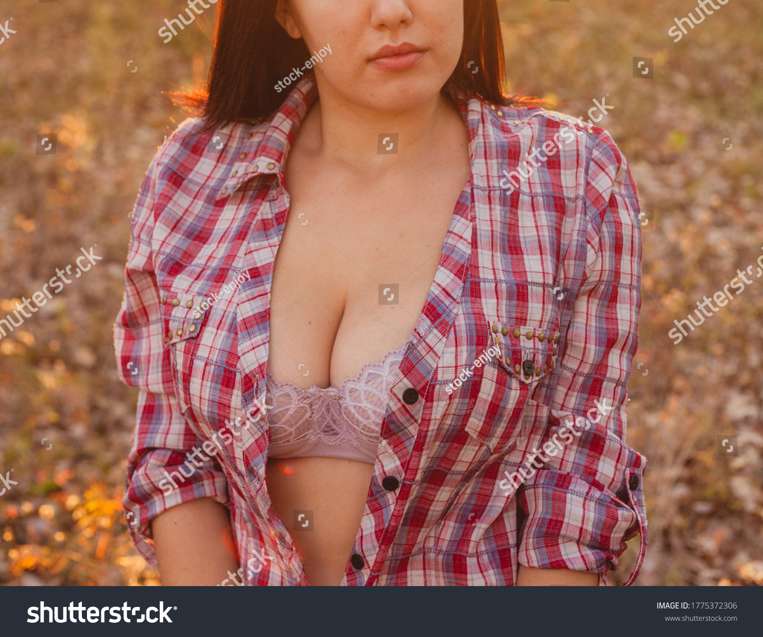 Girl in half open shirt posing outside in the fields