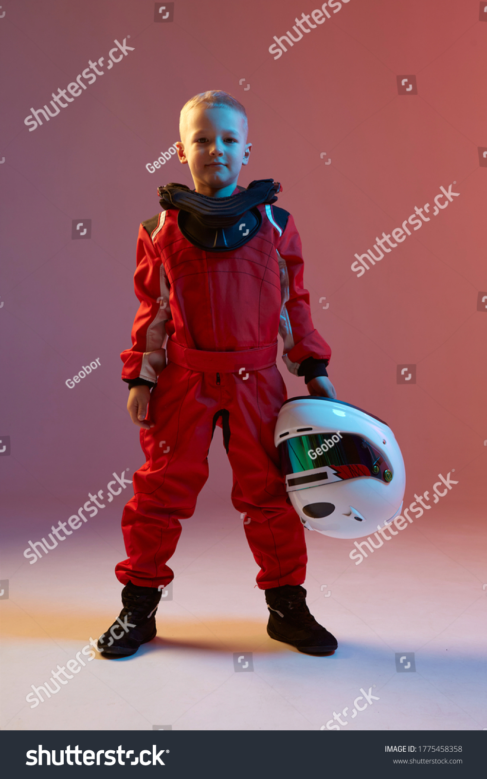 Cool boy child racer with helmet, standing in neon light. Kart racing school poster. Competition announcement #1775458358