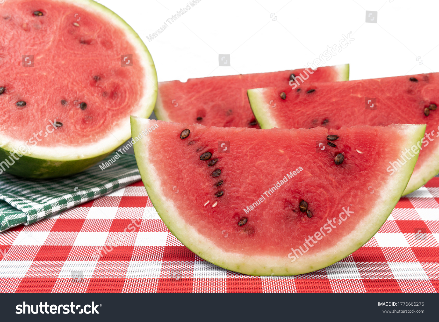 Pieces of watermelon on a red and white tablecloth