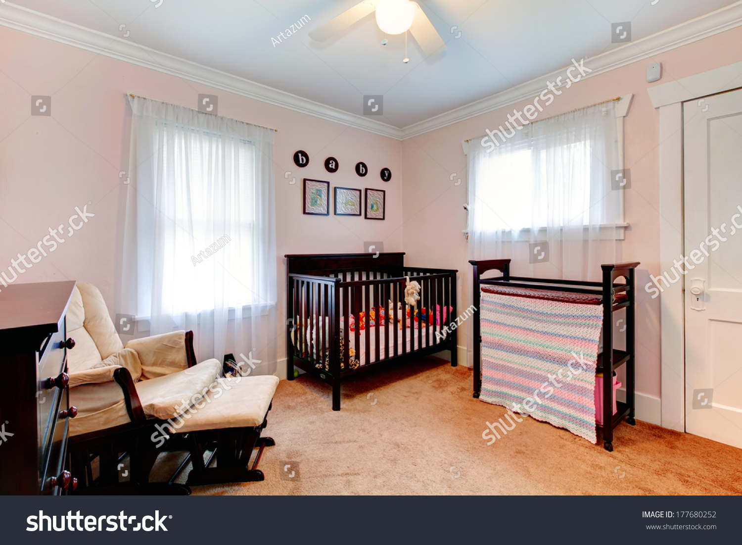 Bright nursery room light pink walls stock photo royalty free bright nursery room with light pink walls carpet floor furnished with dark brown wooden aloadofball Choice Image
