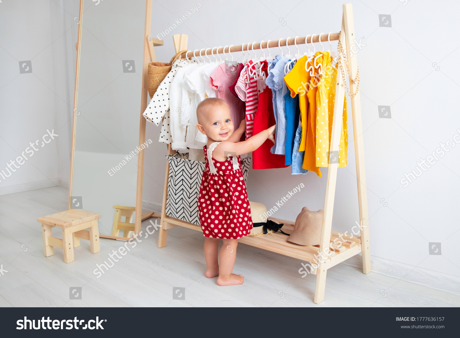 Baby girl stands near a wardrobe and chooses a dress and smiles. Dressing closet with clothes arranged on hangers. Wardrobe of newborn, kids, toddlers, babies full of all clothes. montessori wardrobe. #1777636157