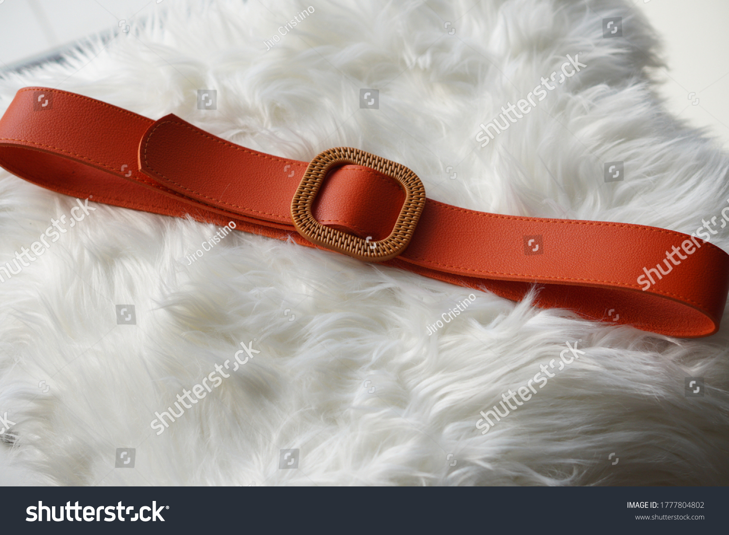 Woman belt with modern buckle upon a white hide blanket. #1777804802