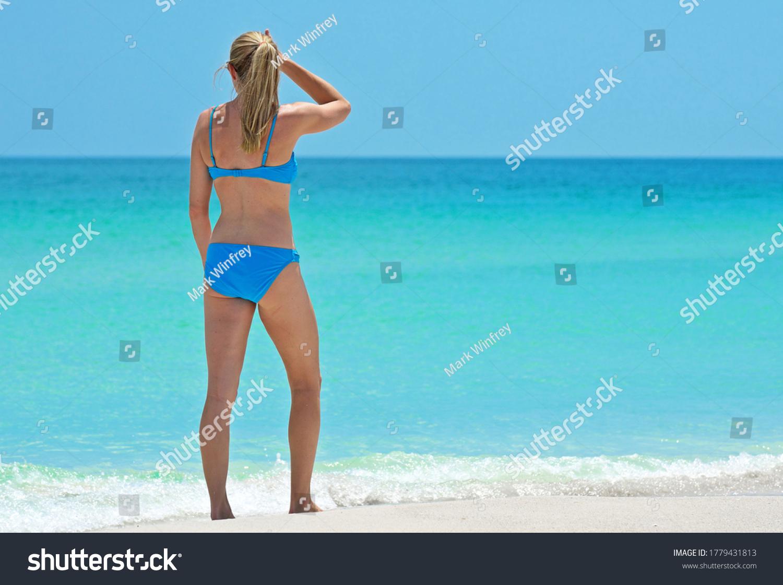 HOLMES BEACH, ANNA MARIA ISLAND, FL / USA - May 1, 2018: Beautiful Young Woman taking a leisure walk on the Beach enjoying a Beautiful Summer Day.