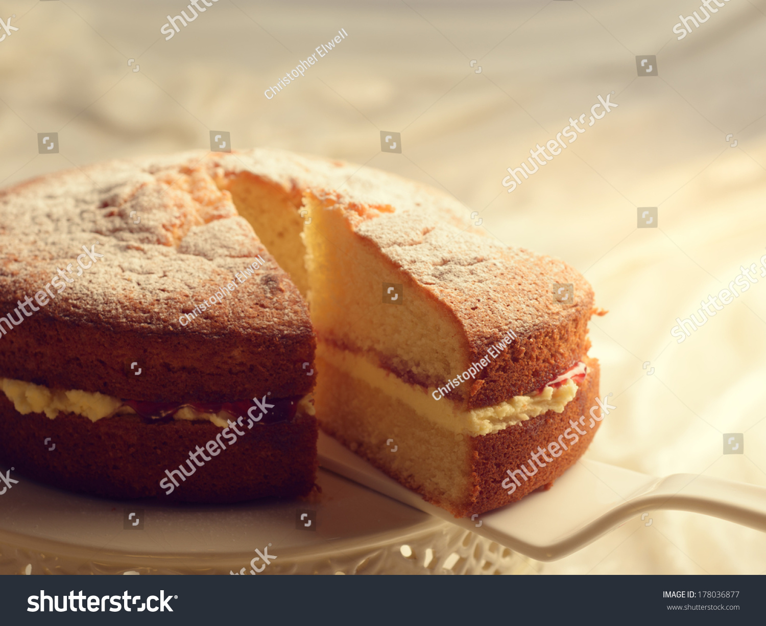 slicing victoria sponge cake revealing jam stock photo