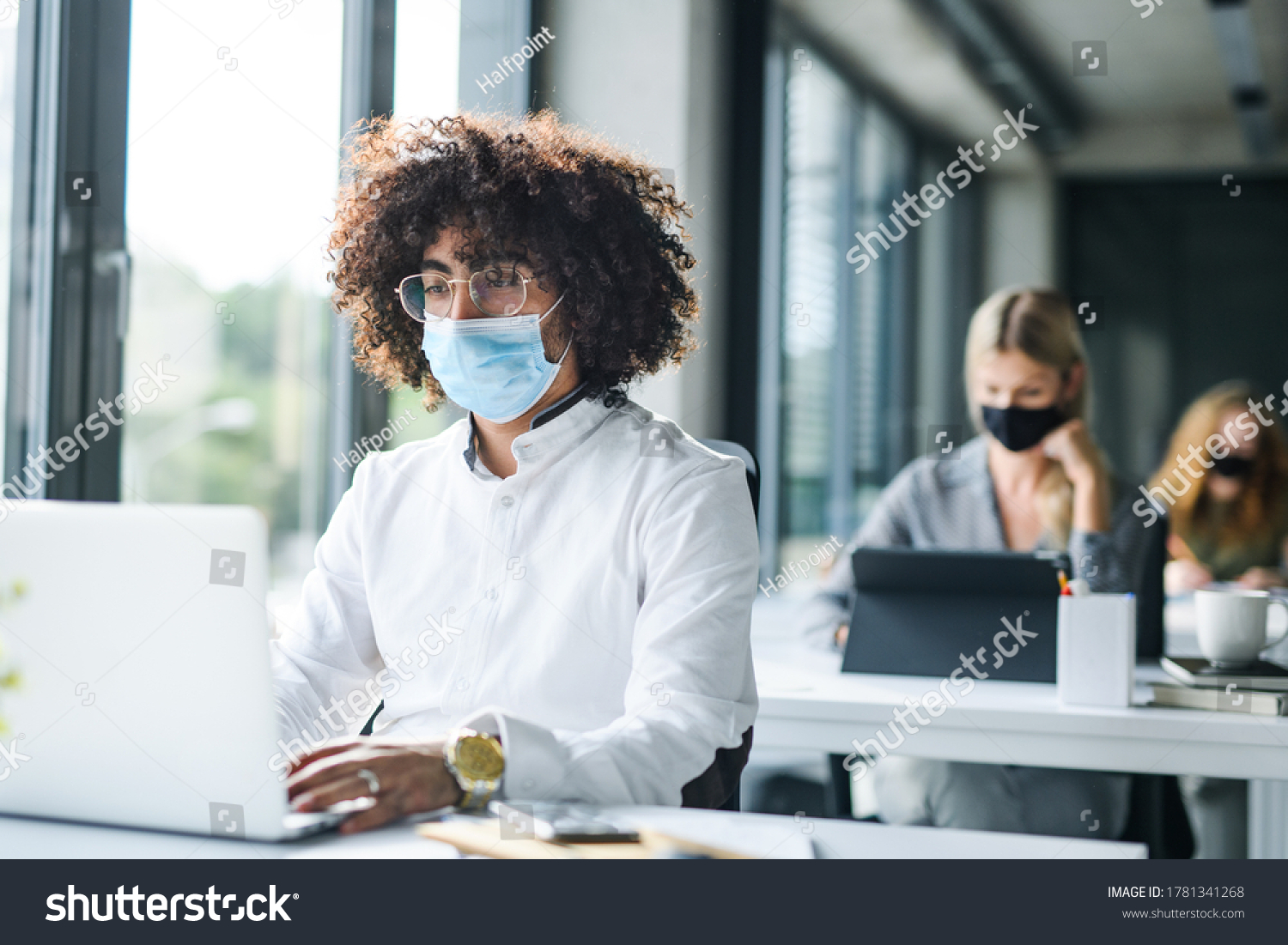 Portrait of young man with face mask back at work in office after lockdown. #1781341268