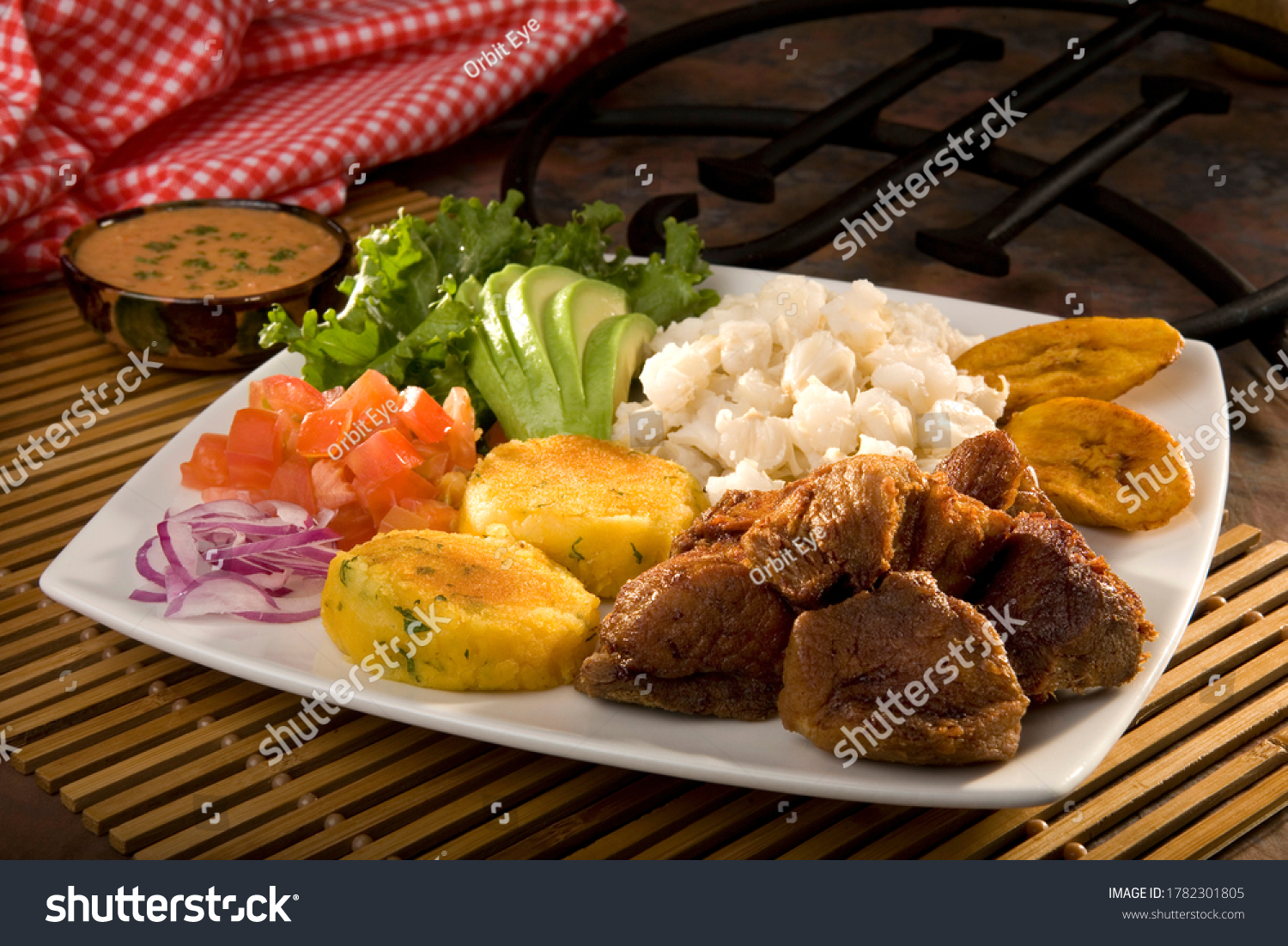 "Traditional and famous Ecuadorian dish called ""Fritada"". It's a braised pork dish that is served always with potato fried cakes, cooked corn kernels with egg, avocado, plantains, tomato and onions. #1782301805"