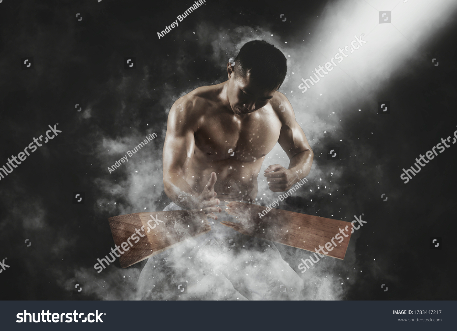 Karate man breaking with hand wooden board on smoke background. Sports banner. Horizontal copy space background #1783447217