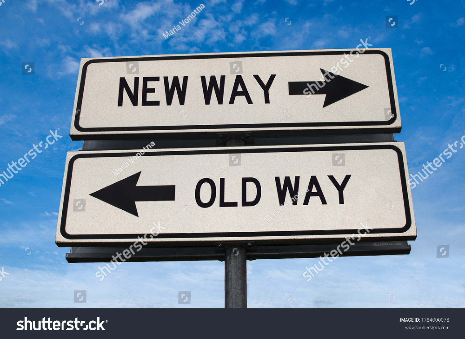 New way versus old way road sign. White two street signs with arrow on metal pole with word. Directional road. Crossroads Road Sign, Two Arrow. Blue sky background. Two way road sign with text. #1784000078
