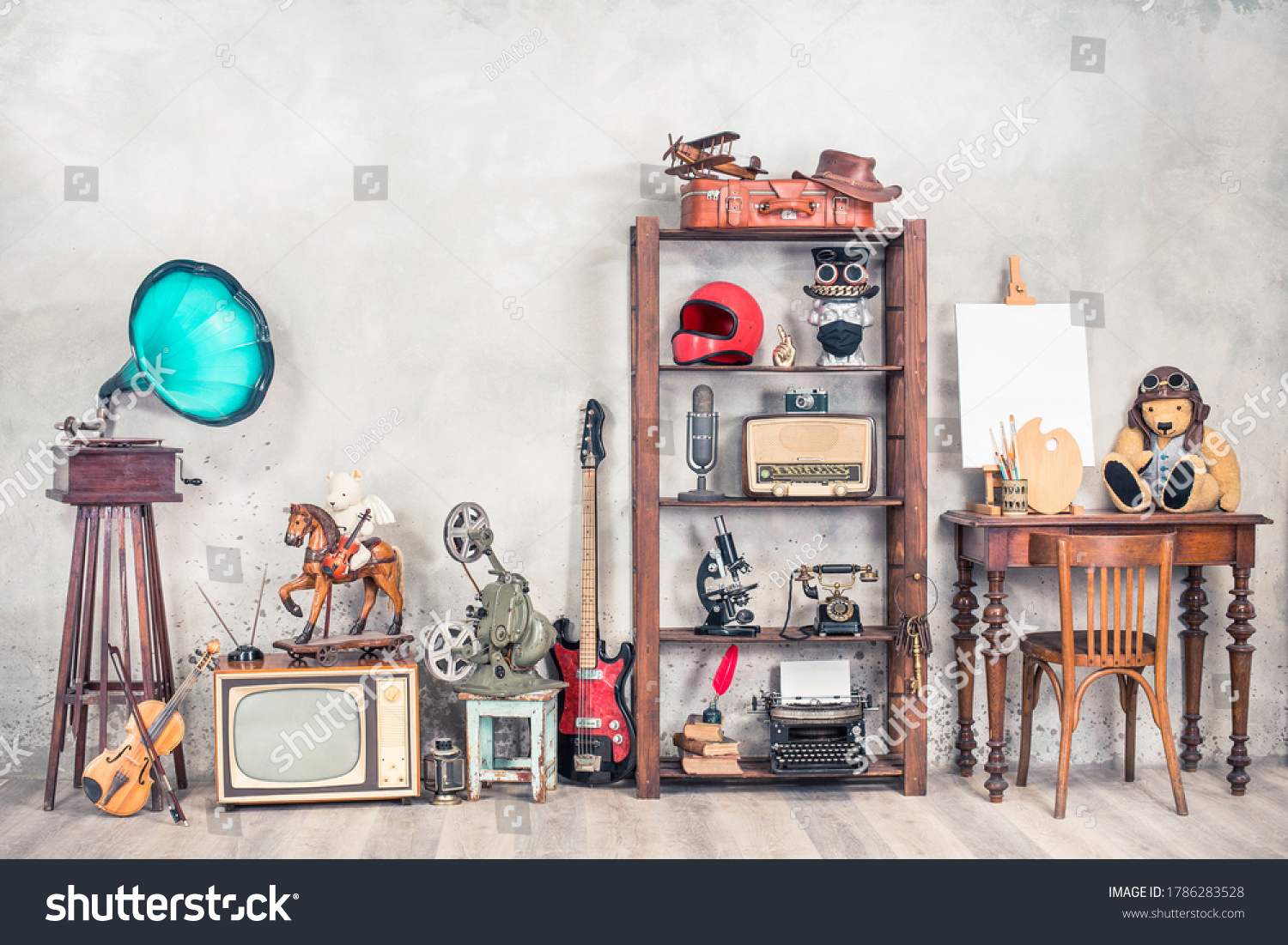 Antique media devices, writers tools, gramophone, film projector, old Teddy Bear toys and white canvas blank on easel, violin and guitar front concrete wall background. Vintage style filtered photo #1786283528