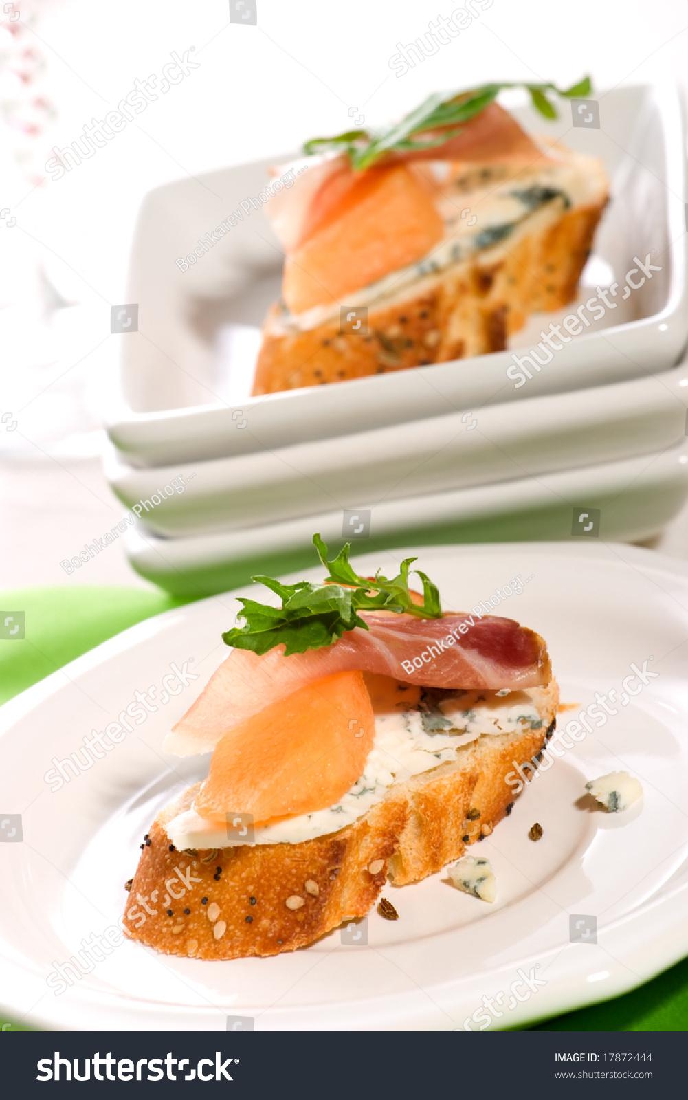 Closeup of two delicious prosciutto canapes sandwiches for Prosciutto canape